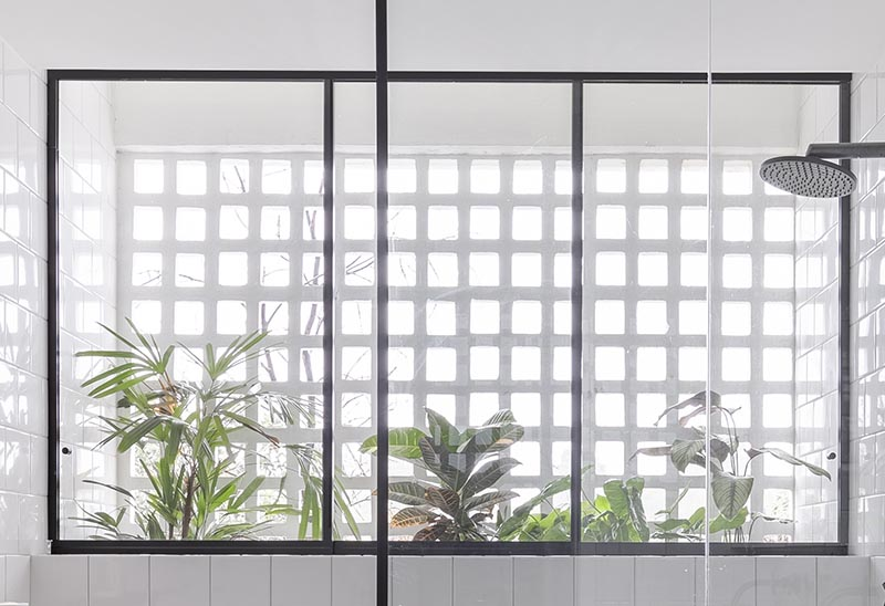 In the shower of this modern bathroom, there's a black-framed three pane window that looks out to a collection of plants that are located between the bathroom wall and the facade of the apartment. #BlackFramedWindow #BathroomDesign #PlantIdeas