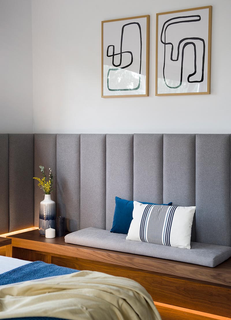 A modern wood bench with a grey cushion and minimalist line artwork on the wall above.