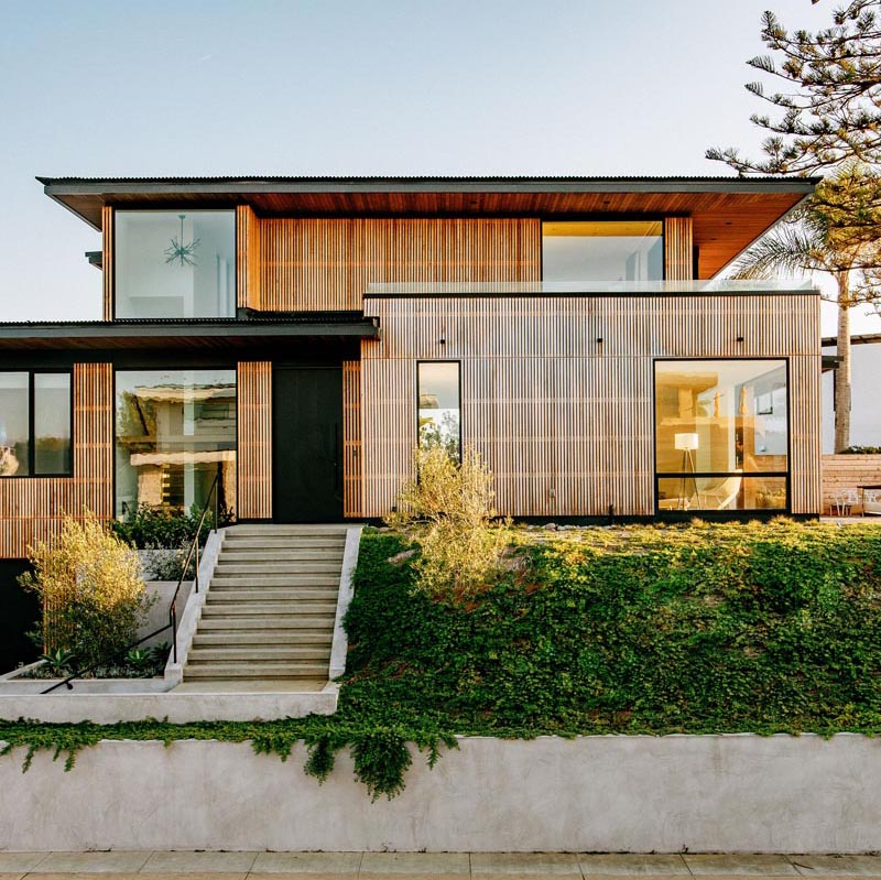 A house with a cedar wood slat facade has black accents and overhanging roof eaves.
