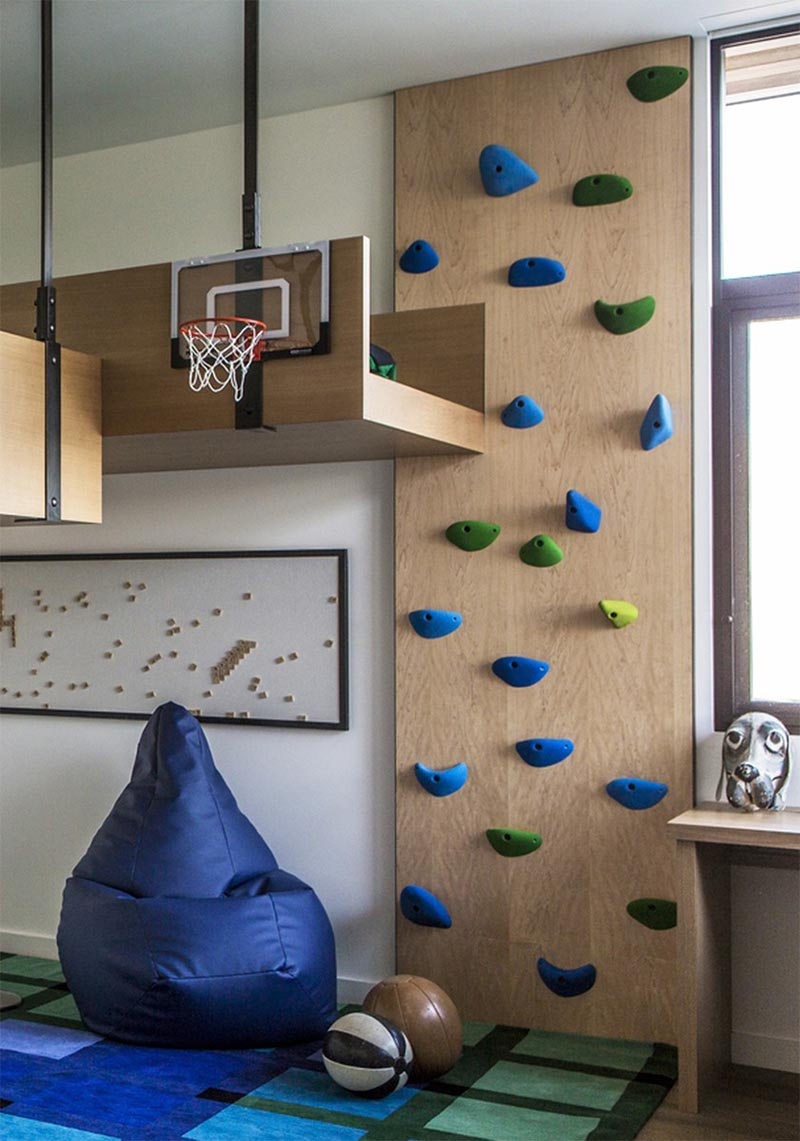 A fun kids bedroom with a rock climbing wall.