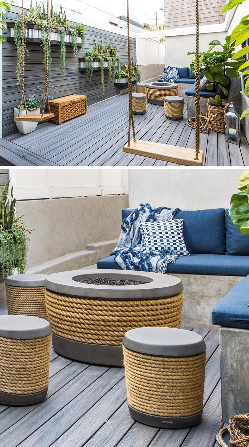 This modern side yard features a wood wall with planters, as well as a deck, both constructed of a Timber Tech material. In the corner, there's an L-shape bench with stools, a pair of swings, and a fire table made from concrete and rope. #SideYard #LandscapeDesign #ModernOutdoorSpace