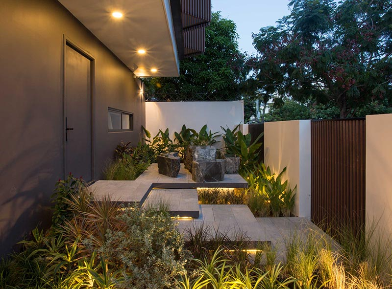 A small landscaped front garden includes overlapping steps, hidden lighting, and a small seating area.