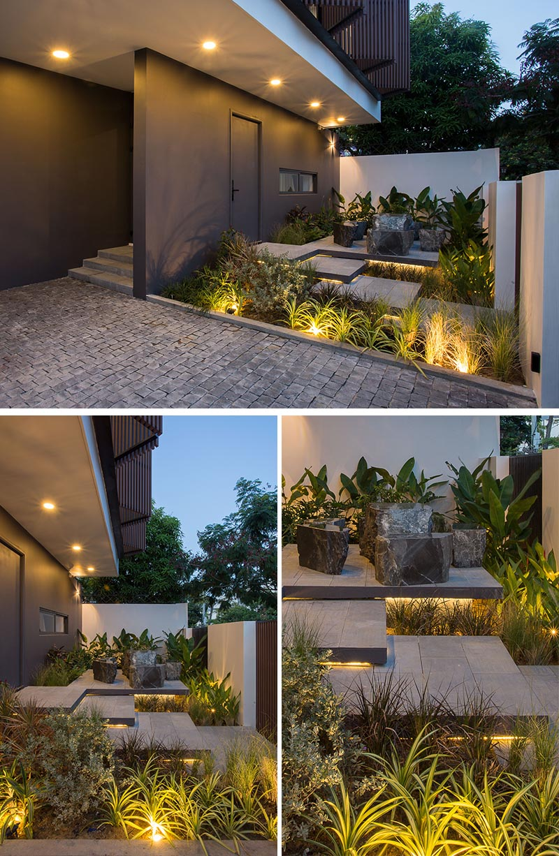 A front garden with hidden lighting that showcases the layered steps, seating area, and lush landscaping.