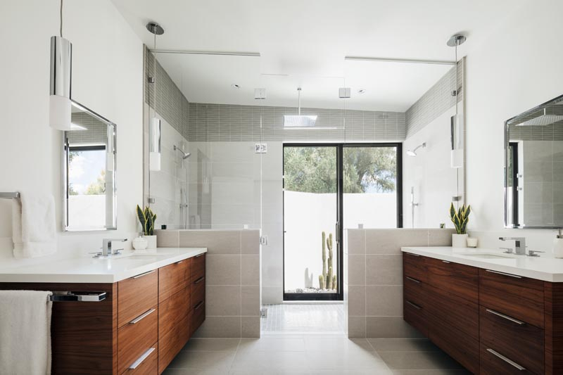 A modern master bathroom with separate dark wood vanities, and a large shower for two.