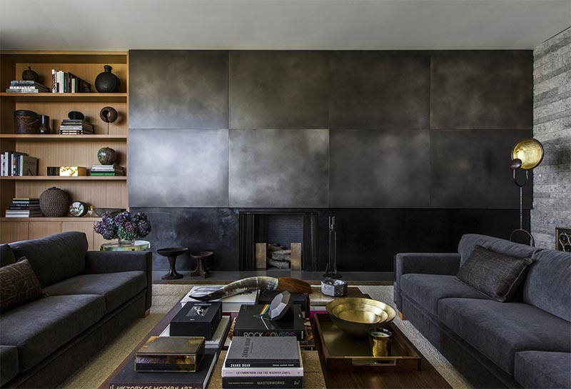 A large metal fireplace surround made from black metal and oversize brass panels in a distinctive silver nitrate finish.