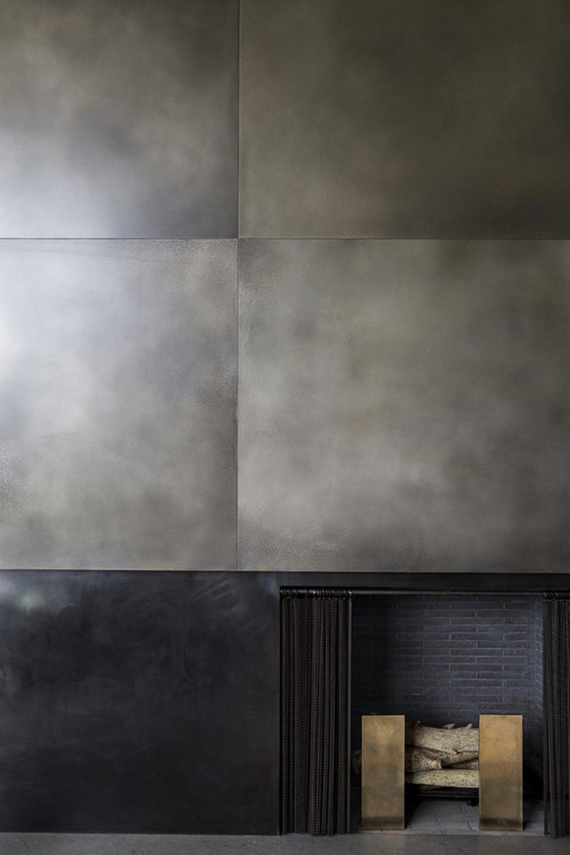 A metal fireplace surround made from brass panels in a silver nitrate finish.