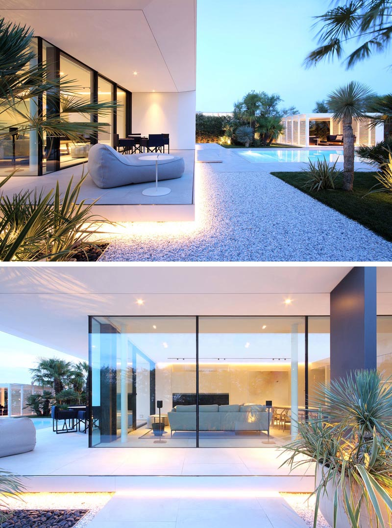 A minimalist white house with outdoor lighting that highlights the crisp architectural lines.