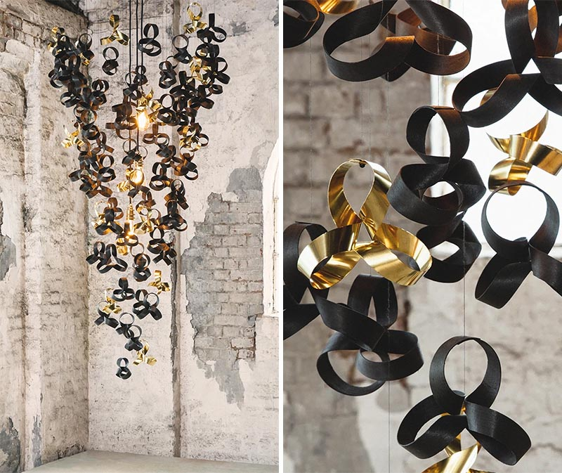 An artistic chandelier made from curls of ebonised oak, ebonised tulip wood, and reflective solid brass.