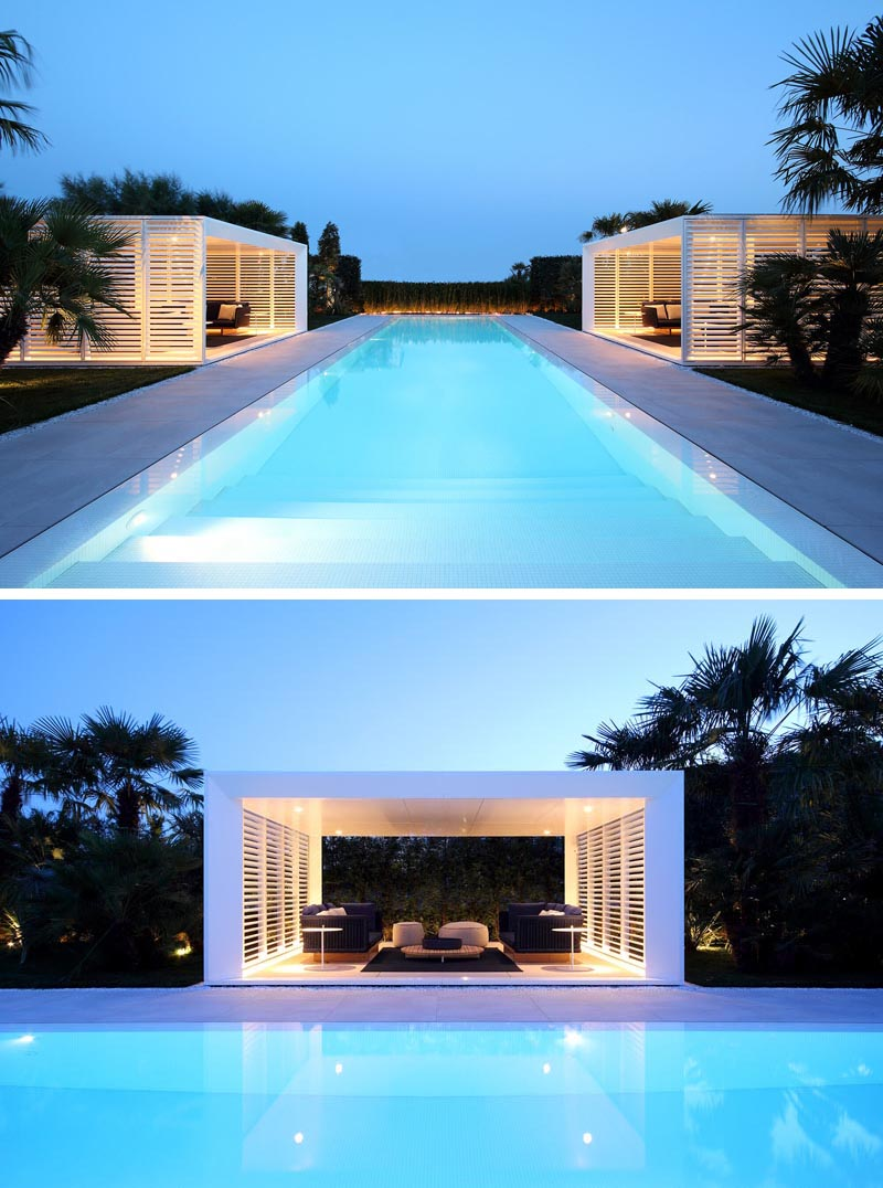 A pair of modern cabanas flank a long infinity edge swimming pool.