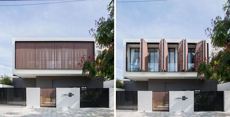 Wood shutters cover the second floor of this modern house.