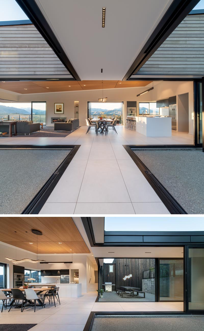 Retractable glass walls connect the interior spaces of this house with an alfresco dining area and a patio.