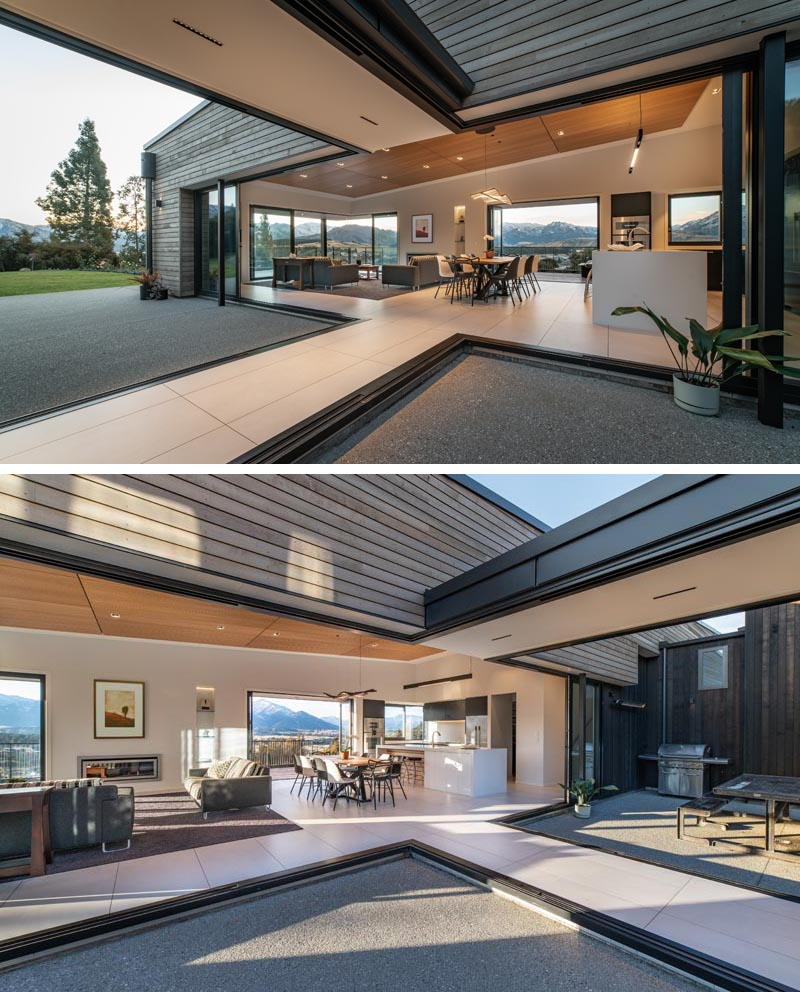 Retractable glass walls open up a hallway and open plan living spaces with the outdoors.