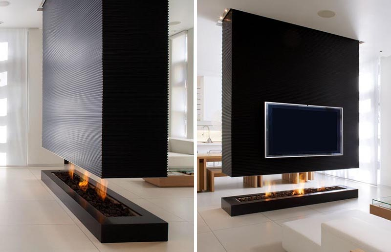 A black room divider separates the living room from the dining room, and includes a fireplace and a recessed television.