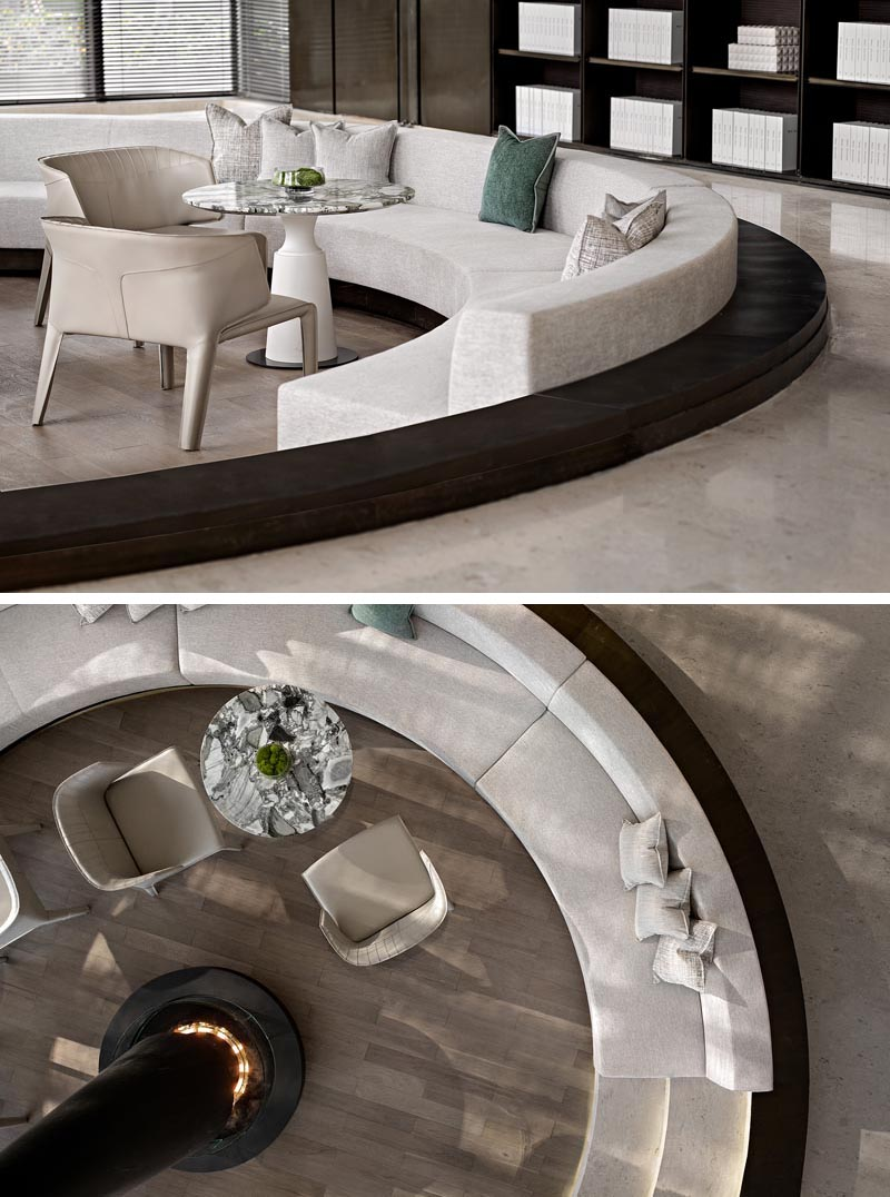 This sunken conversation pit, which was designed as a warm and pleasant space for potential customers to talk, offers custom seating that wraps around the interior of the circular shape, with enough room for small tables to also be included. #ConversationPit #SunkenSeating #InteriorDesign #Fireplace