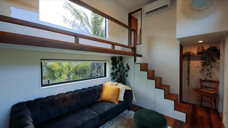 This tiny house has stairs that connect to a walkway that leads to the two bedrooms.