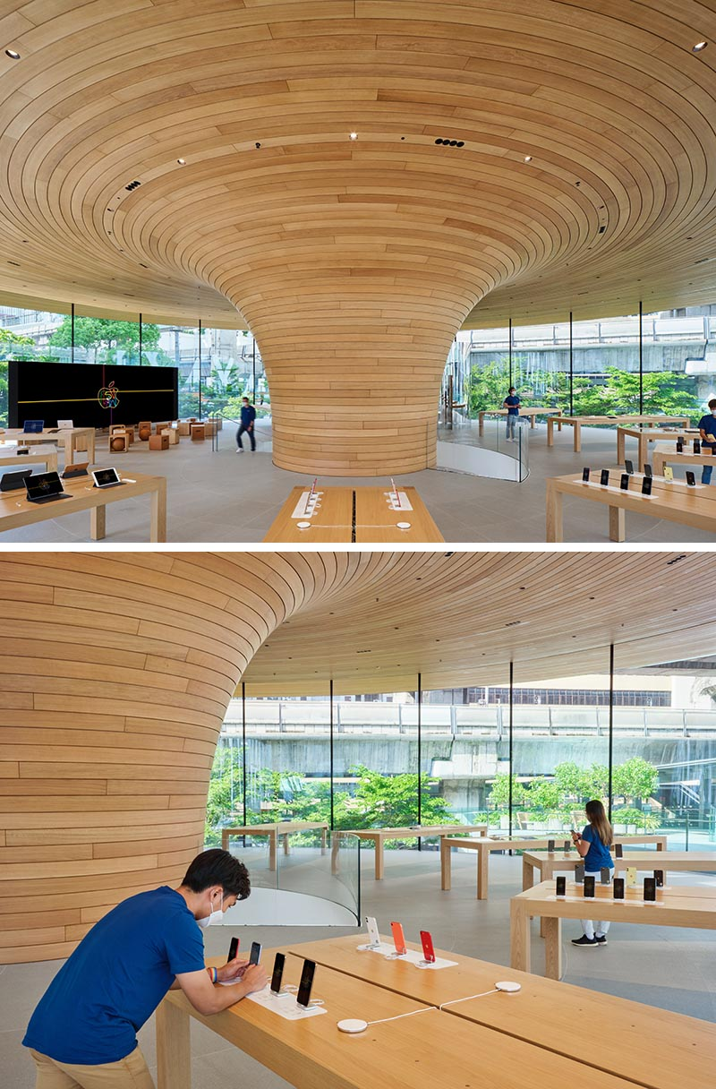 Apple Central World includes an eye-catching cylindrical glass facade with views of a large sculptural wood core.