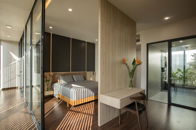 A room divider separates the sleeping area from the closet and creates room for a floating desk.