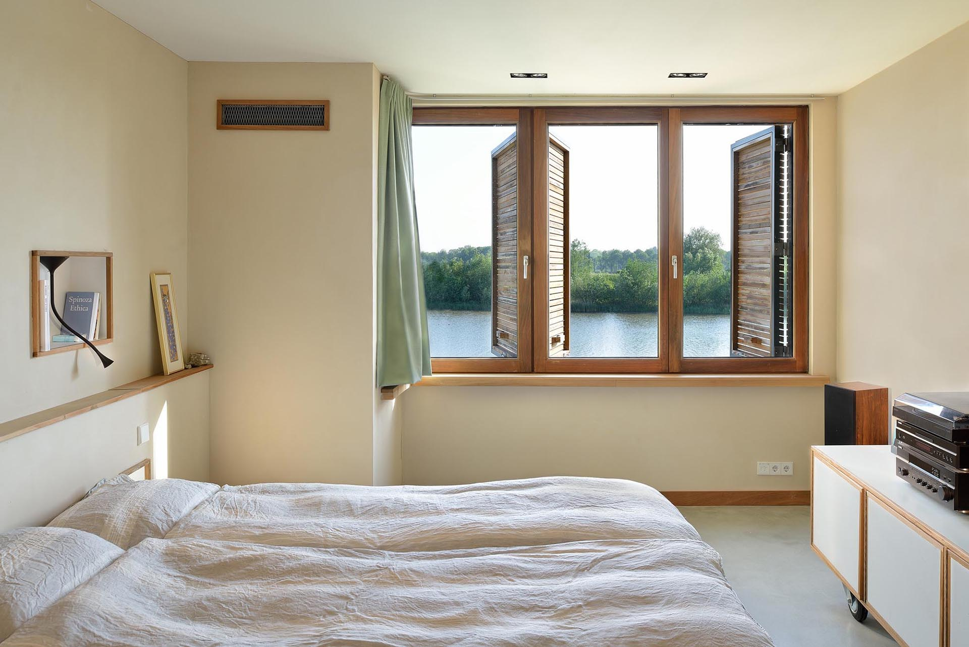 A neutral bedroom with wood window shutters.