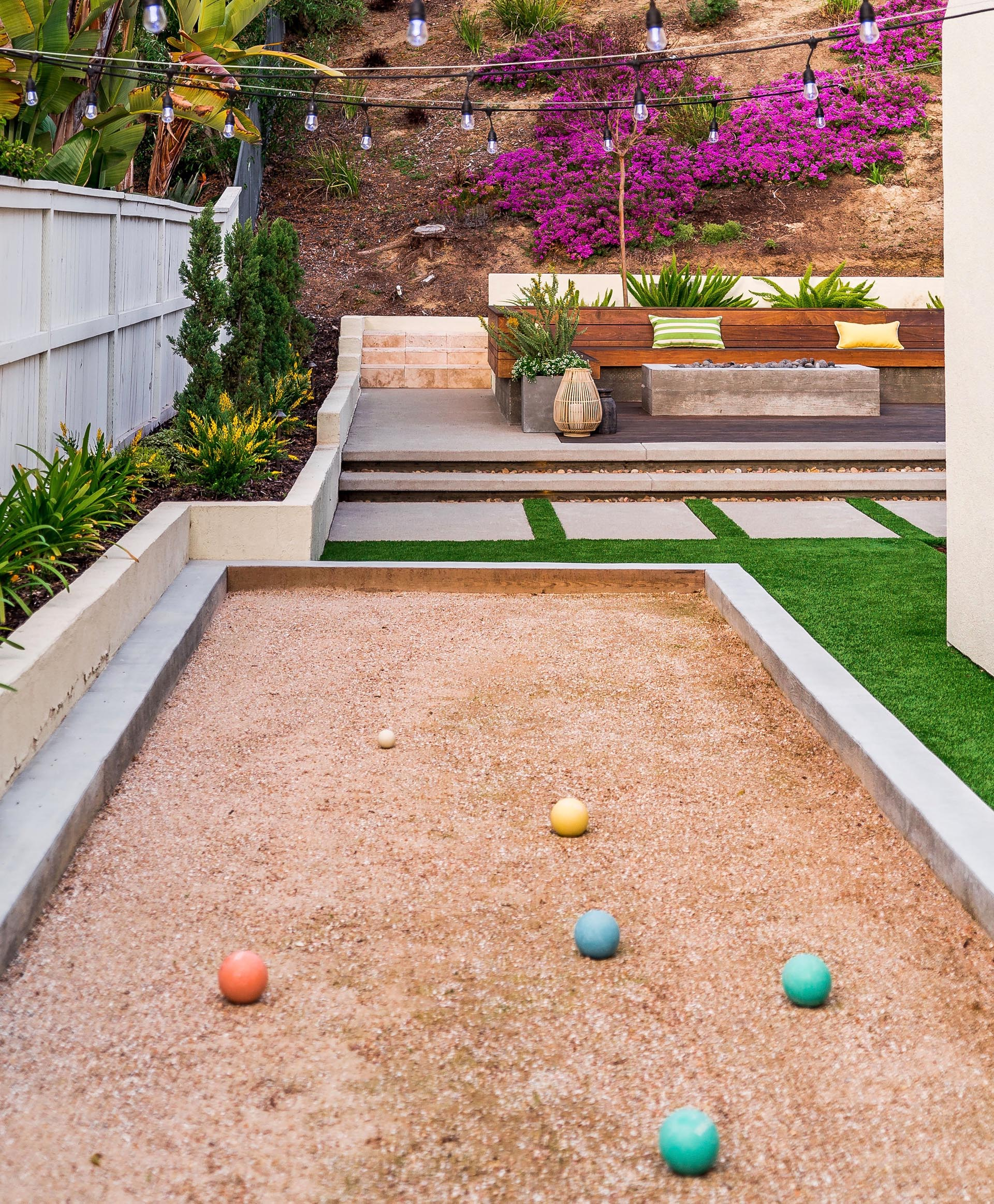 A modern yard with a raised seating area and fire pit, and a bocce court.