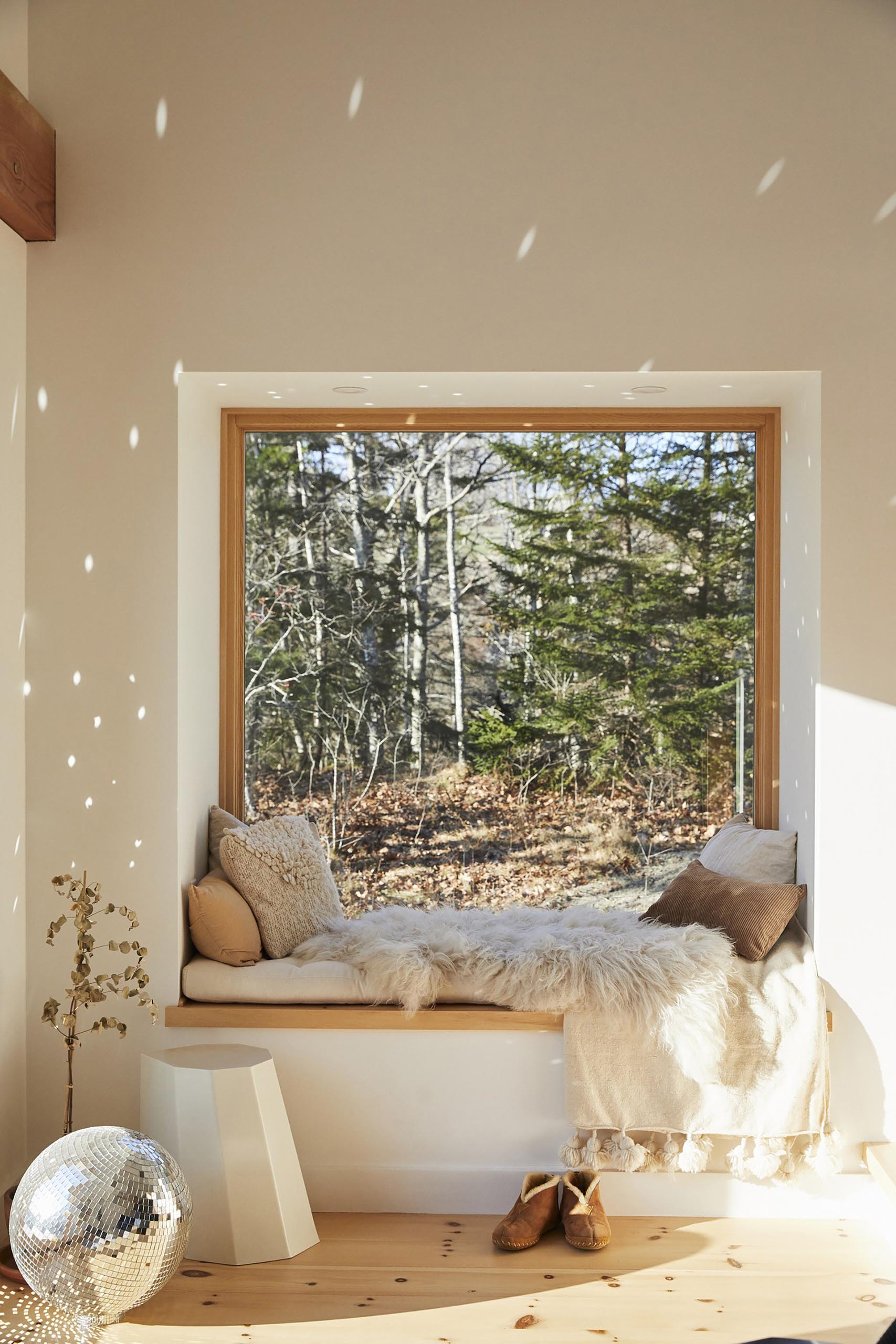 A cozy window seat with tree views, soft pillows and blankets, and a mirror ball that scatters light.