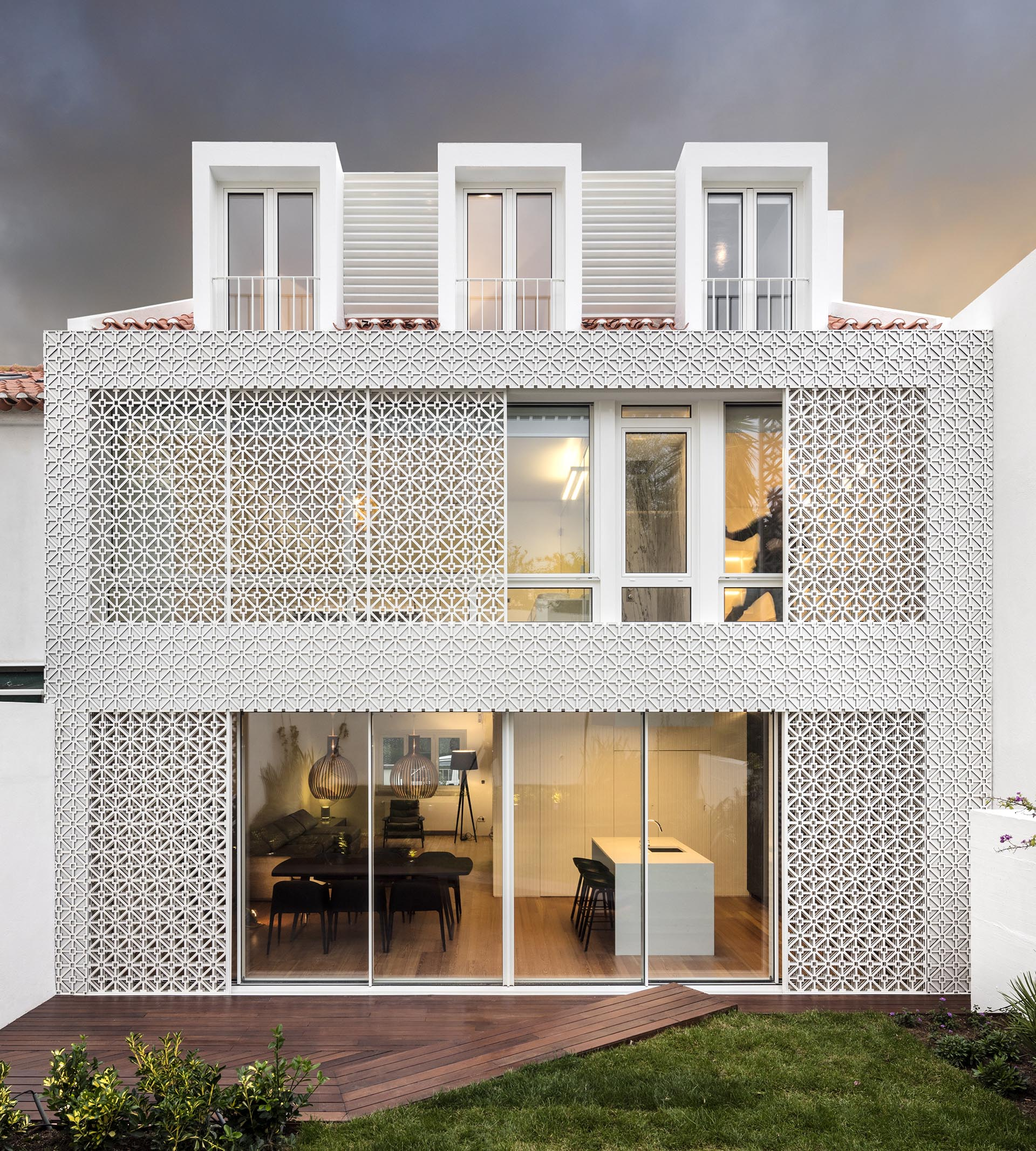 Sliding patterned screens provide shade, security, and a decorative element to this house.