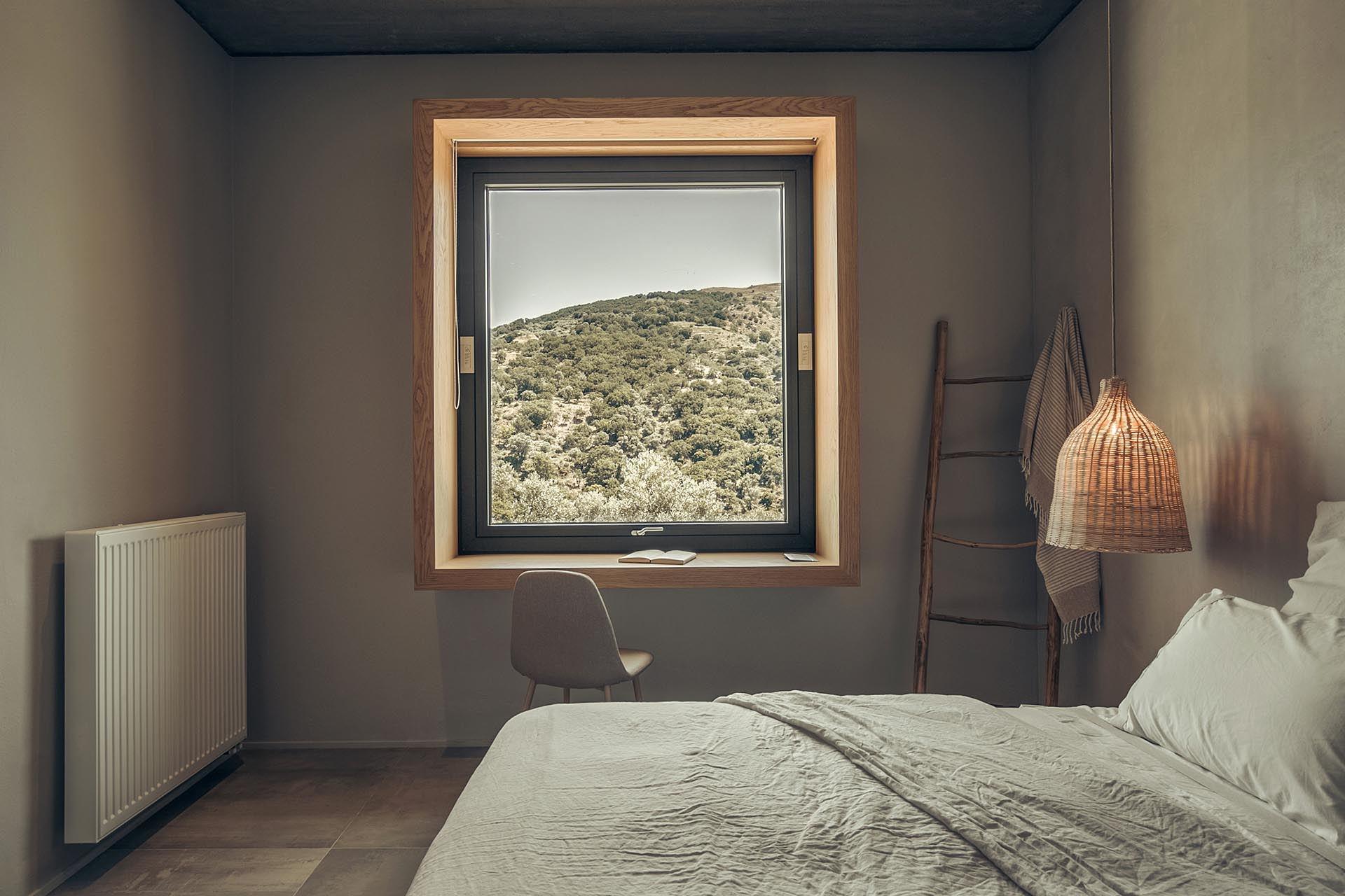 A deep wood window frame showcases the view and acts as a desk.