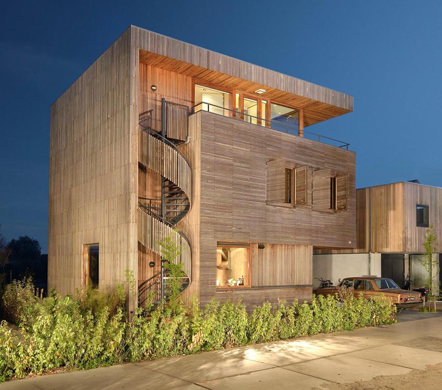 A modern wood house with an exterior spiral staircase covered in wood slats.