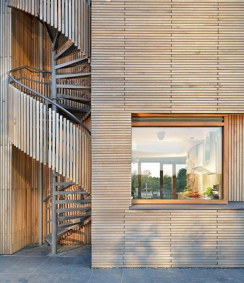 A modern wood house has an exterior spiral staircase that's covered in wood slats.