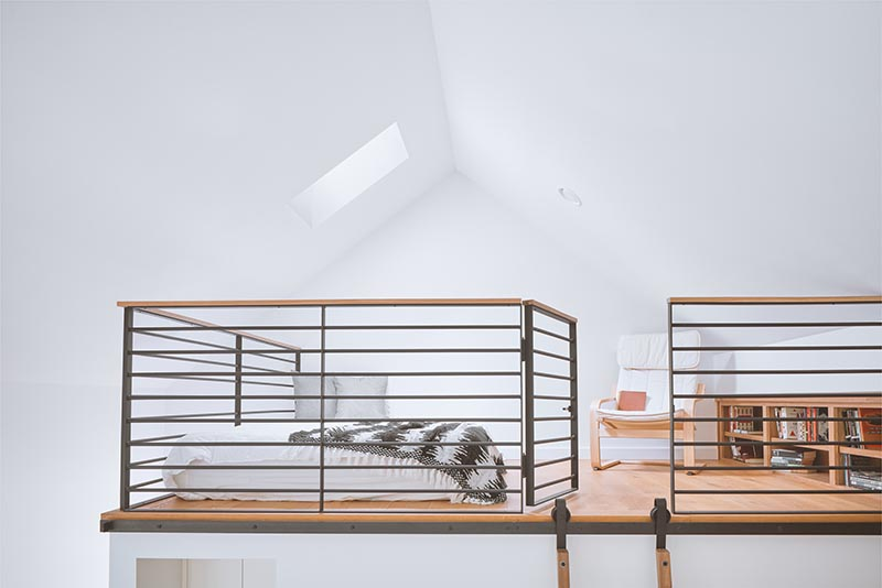 A lofted guest suite within a home office designed as a writer's studio