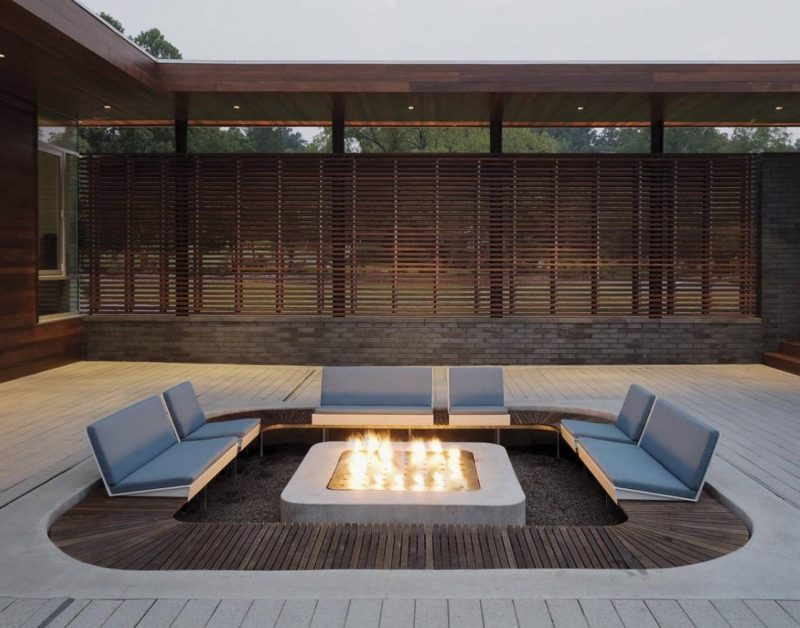 A modern outdoor conversation pit with a square shape and custom seating that's focused on the fire.