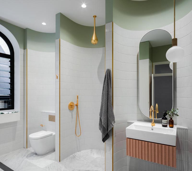 Curved walls in this modern bathroom divide the space into areas for a vanity, the shower, and the toilet.