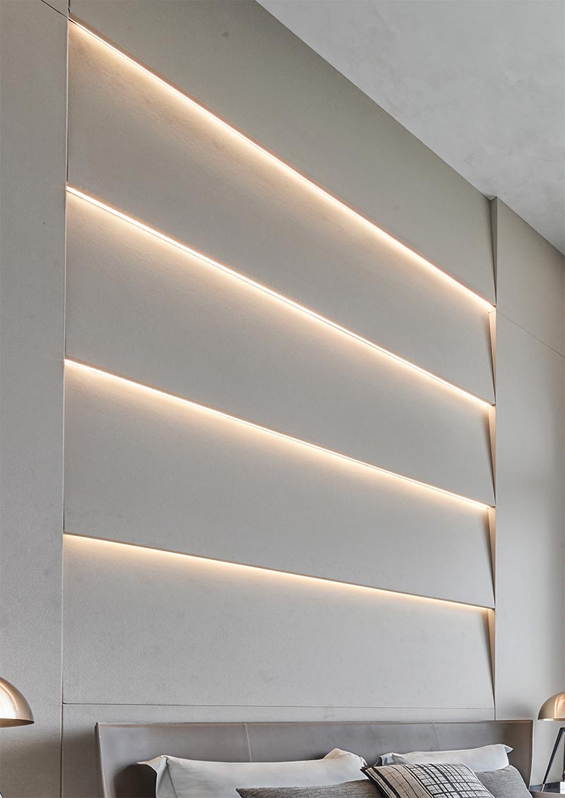 An accent wall with angled sections that also have hidden lighting that creates a soft glow.