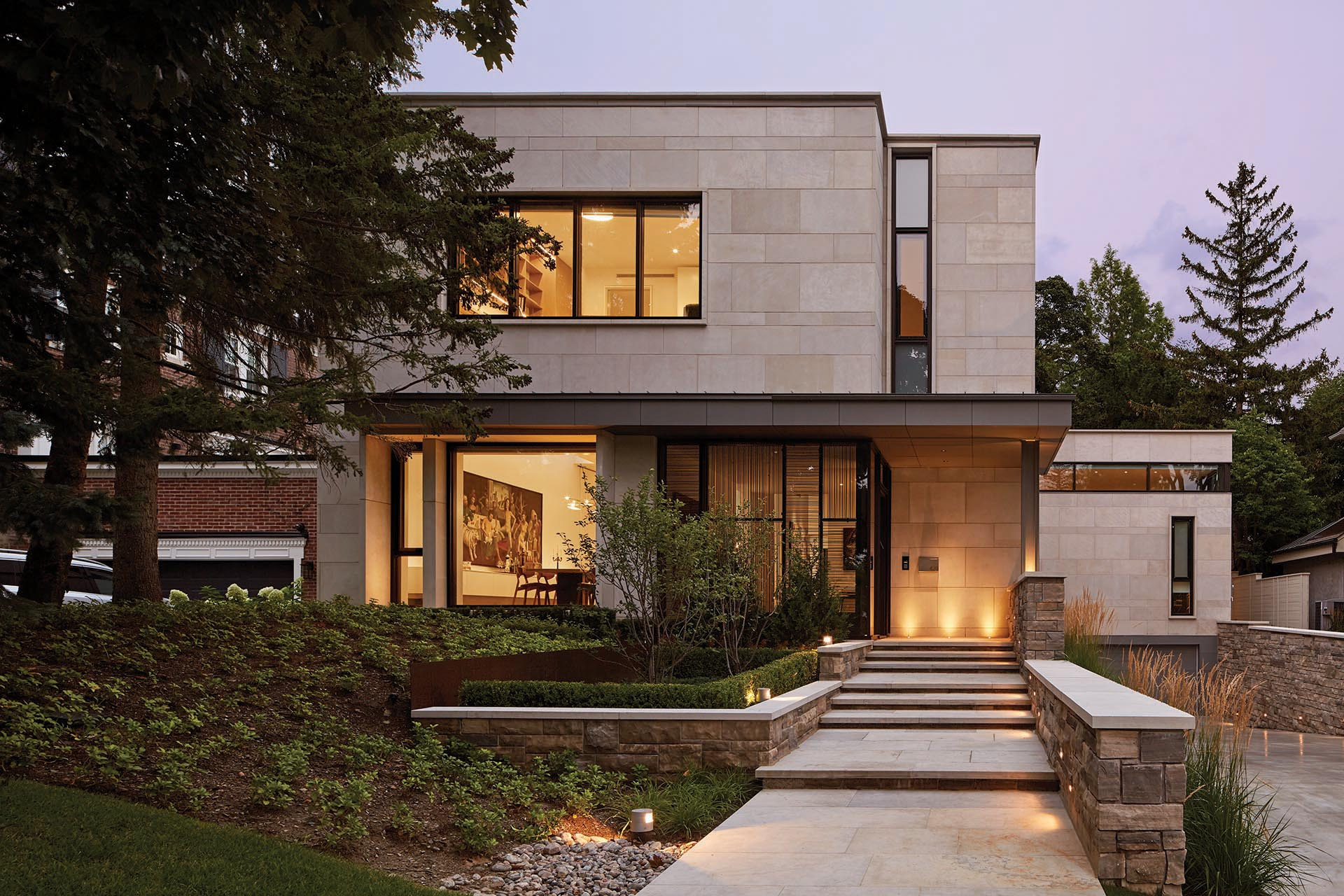 Indiana Limestone and split faced Ontario Algonquin stone clad the exterior of this modern house.