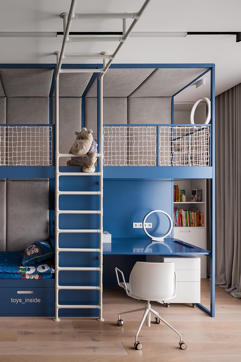 A kids bedroom with a climbing gym, homework station, and a lofted play space.