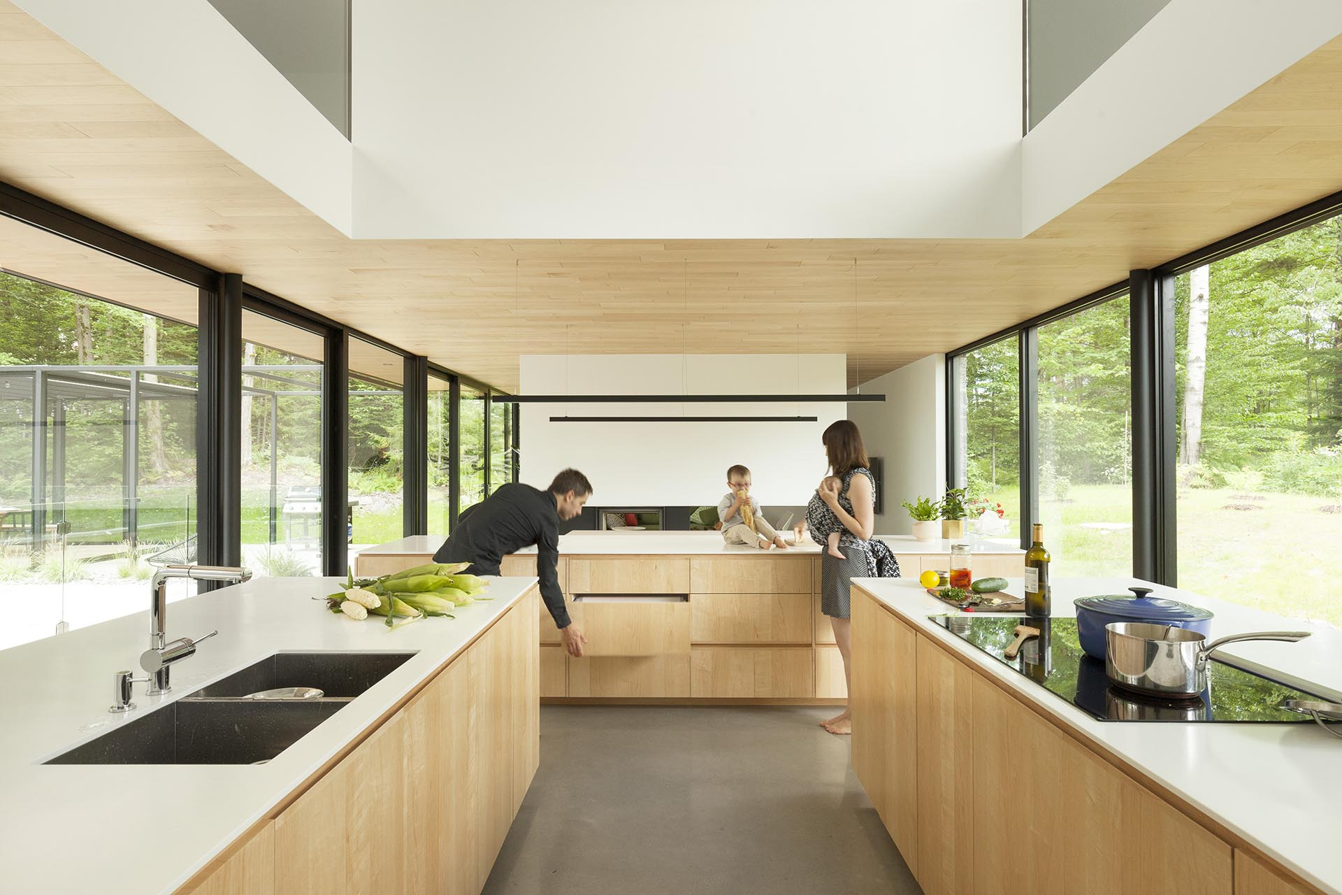 A modern kitchen design with three islands, a double height ceiling, and a wall of cabinets.