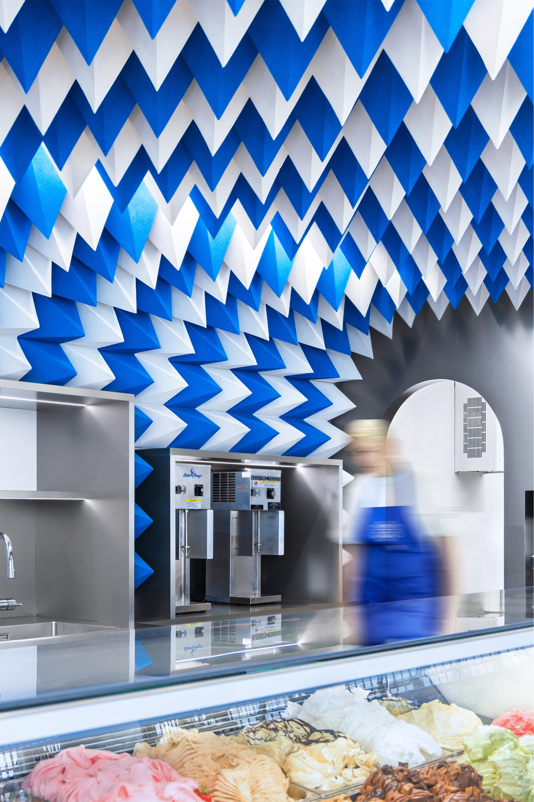 A modern ice cream store with a sculptural ceiling installation