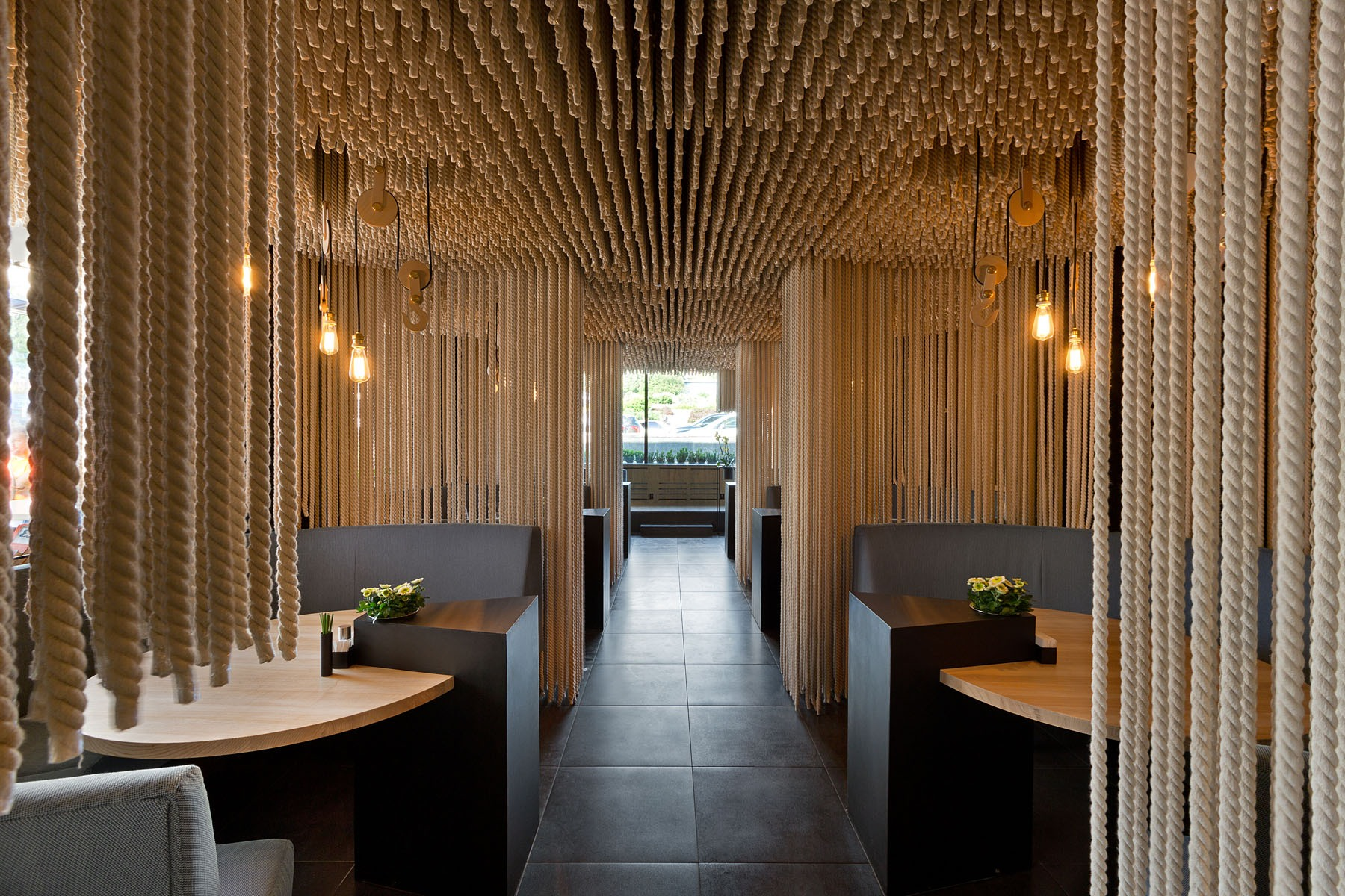 Rope was used to create room dividers and a ceiling installation in a modern restaurant.