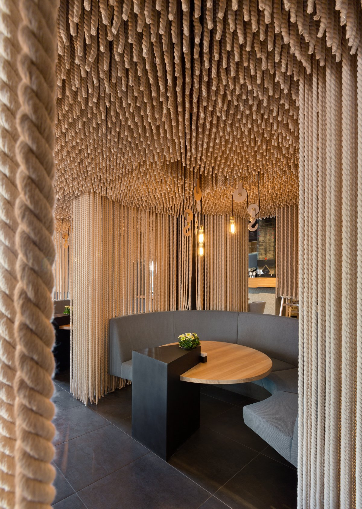 A modern restaurant with rope room dividers and ceiling installation.