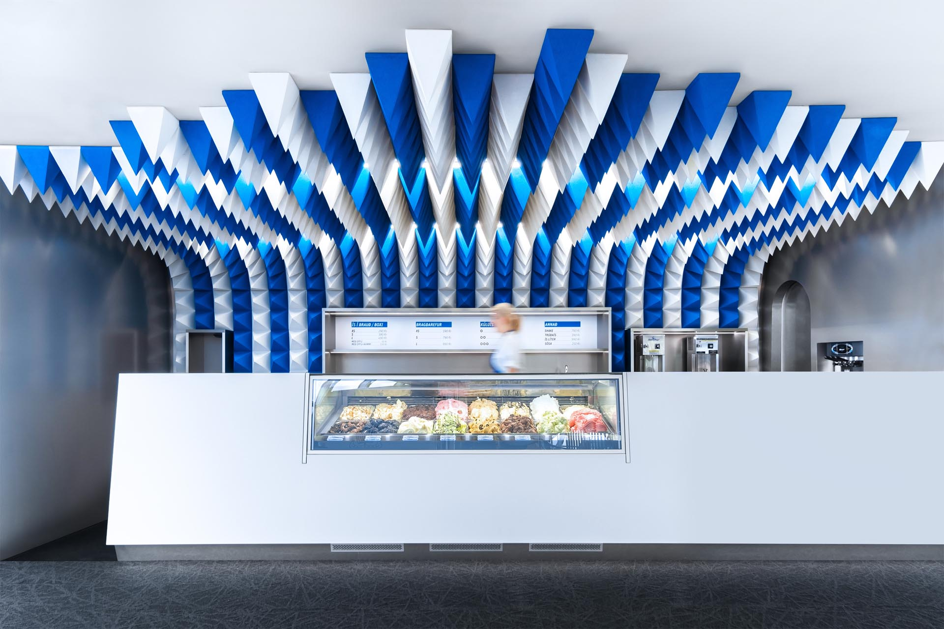 A sculptural ceiling installation made from blue and white foam pyramids.