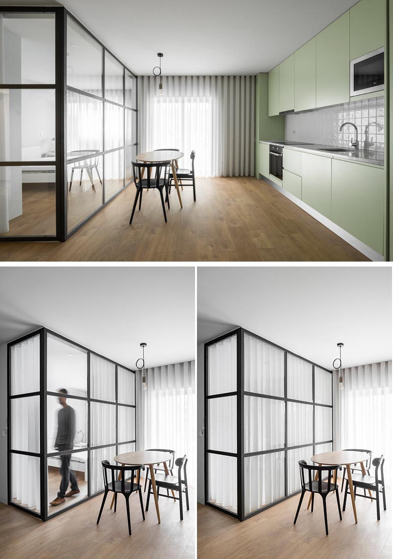 A glass enclosed bedroom with black frames allows light to travel from the bedroom through to the dining room and kitchen.
