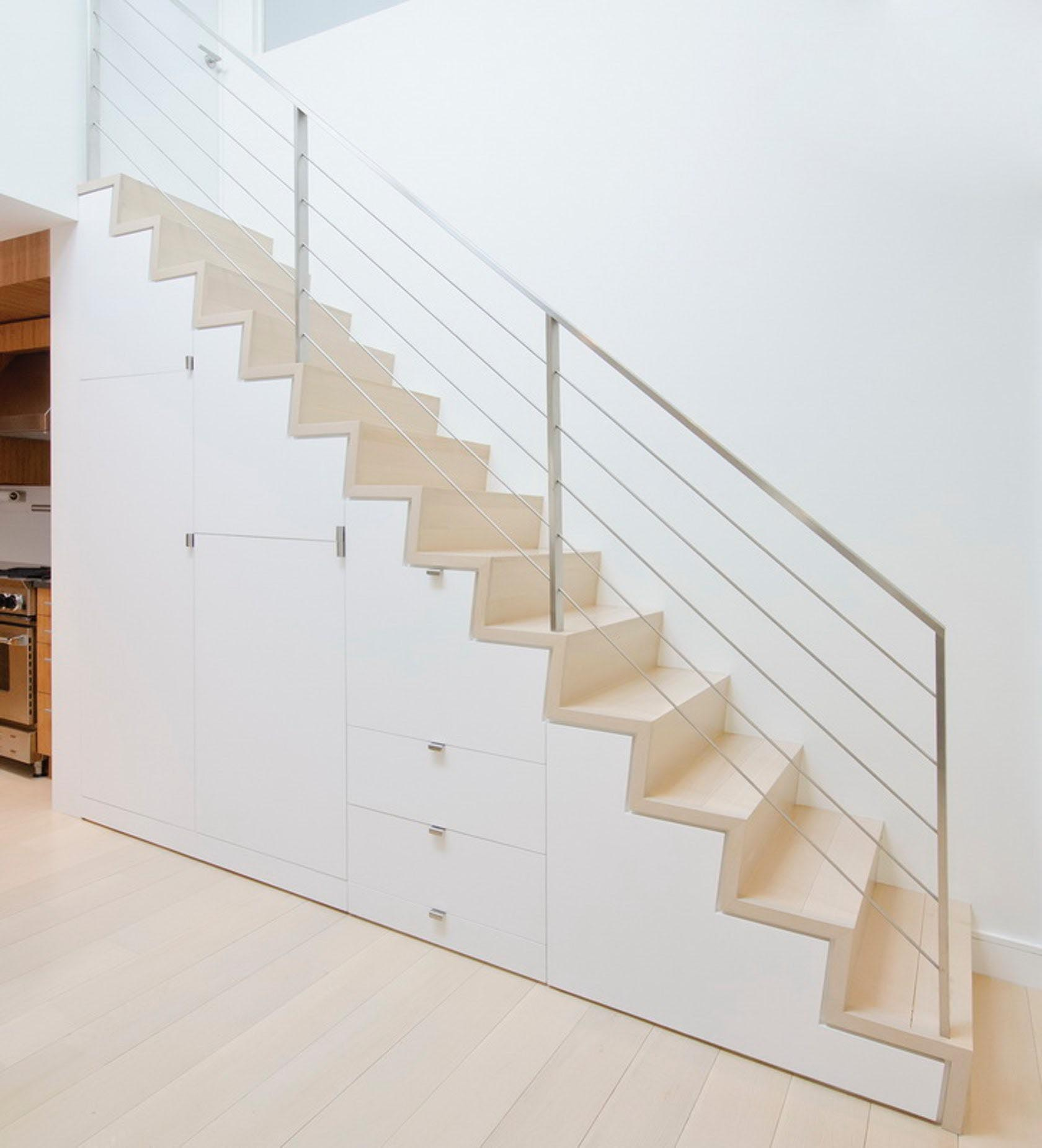 Under stair storage made from white cabinetry.