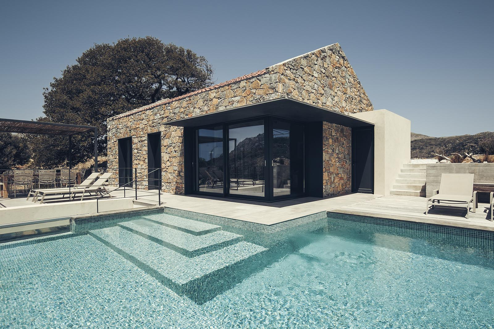 A summer house with black metal accents that contrast the stone walls.