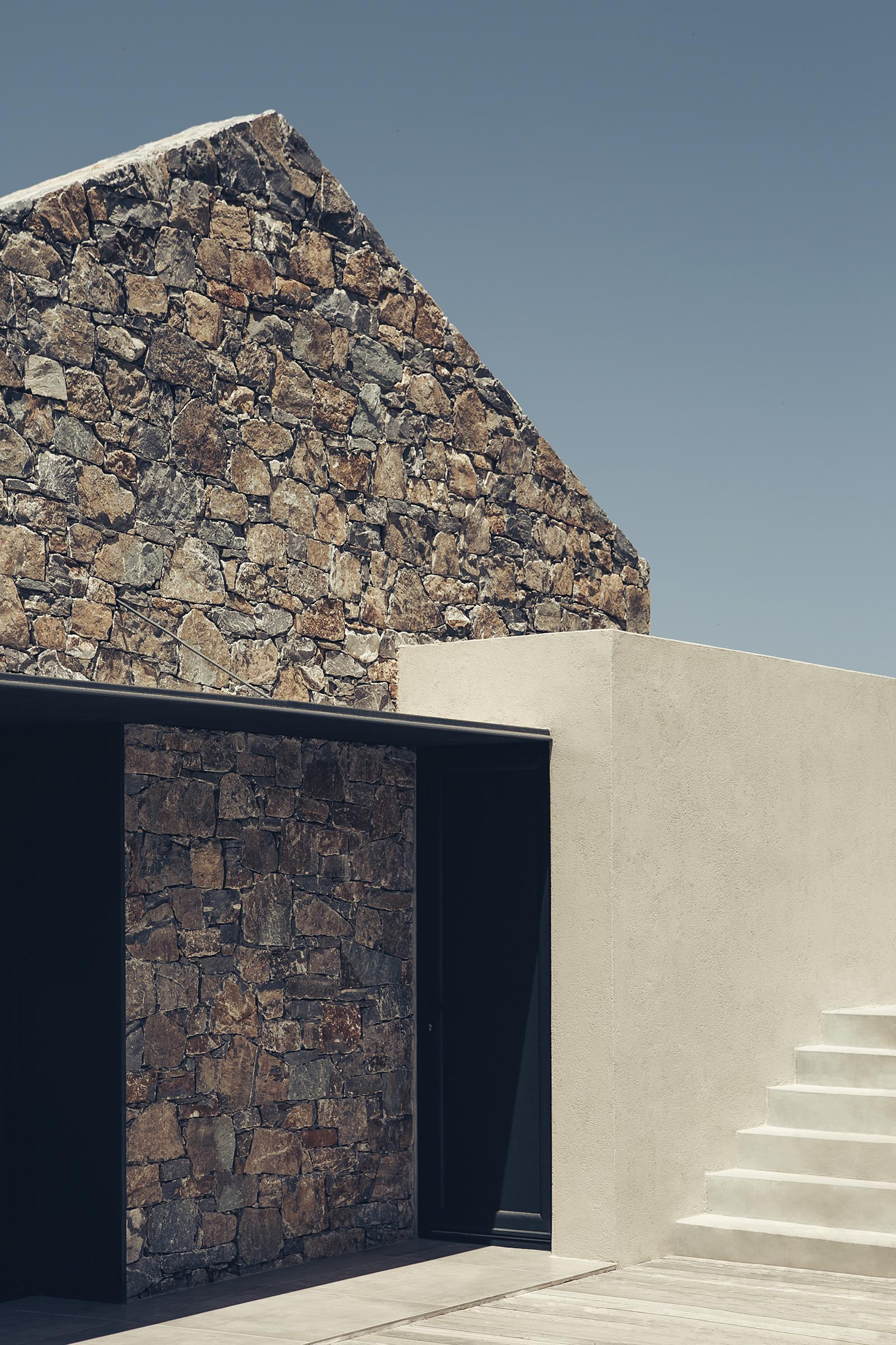Black metal accents contrast the stonework of this contemporary house.