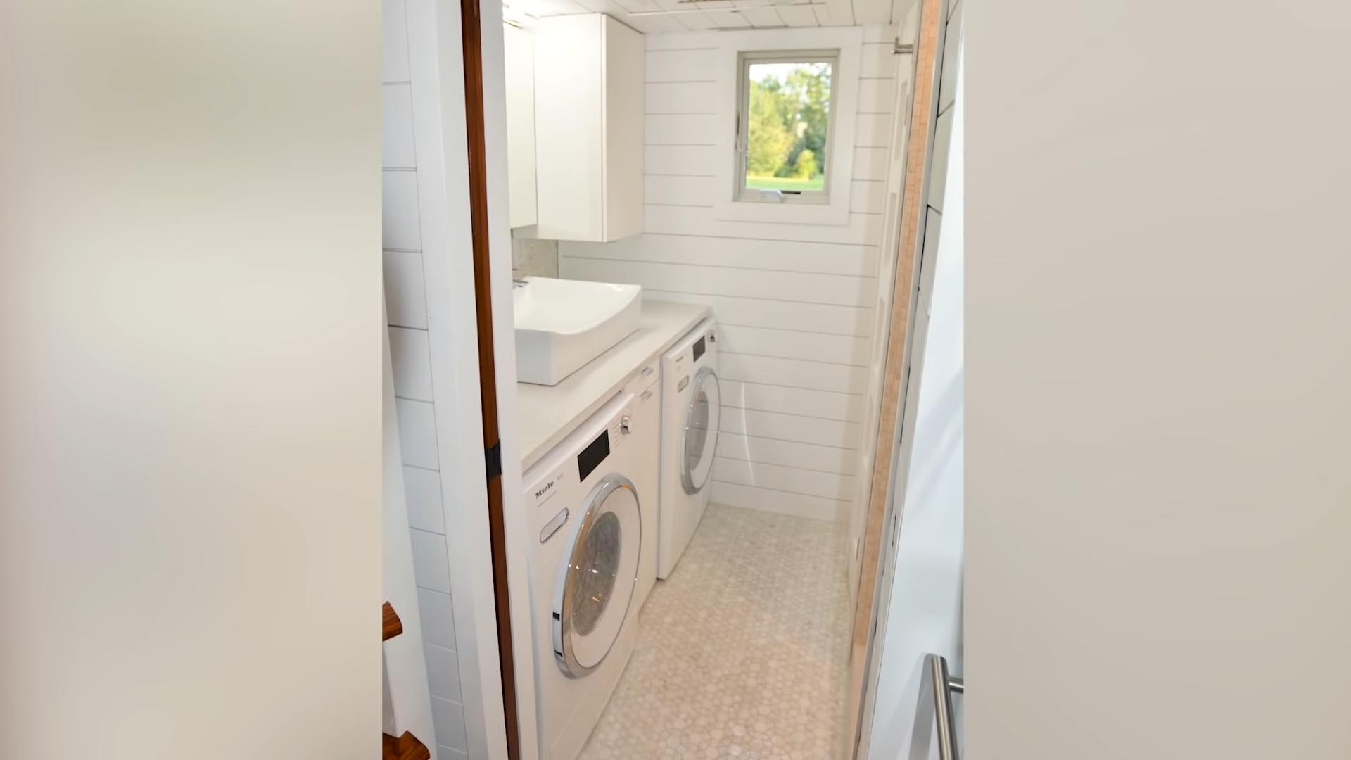 A tiny house bathroom with washer/dryer, and walk-in shower.