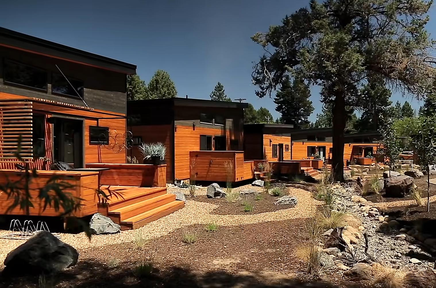 A modern tiny house community with homes and paths connecting them to the landscaping.
