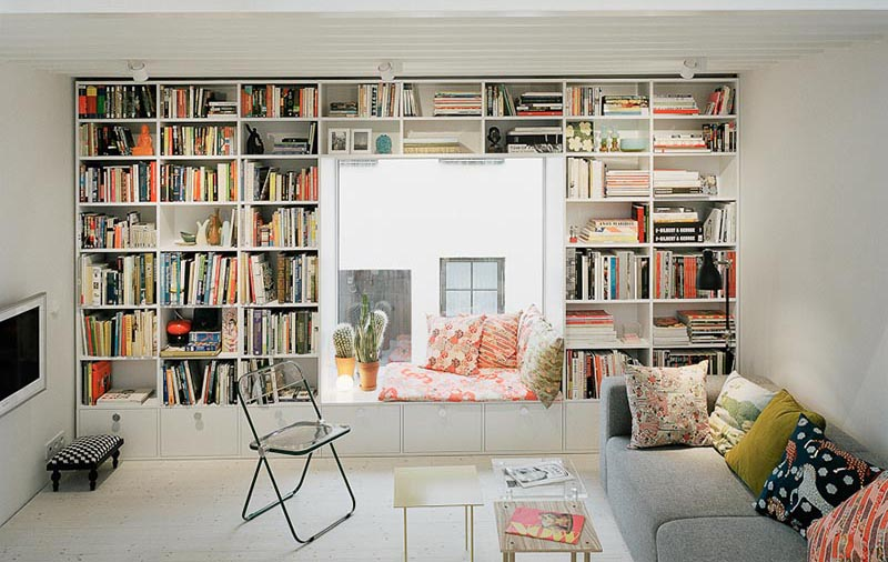 A cozy window seat surrounded by shelves.