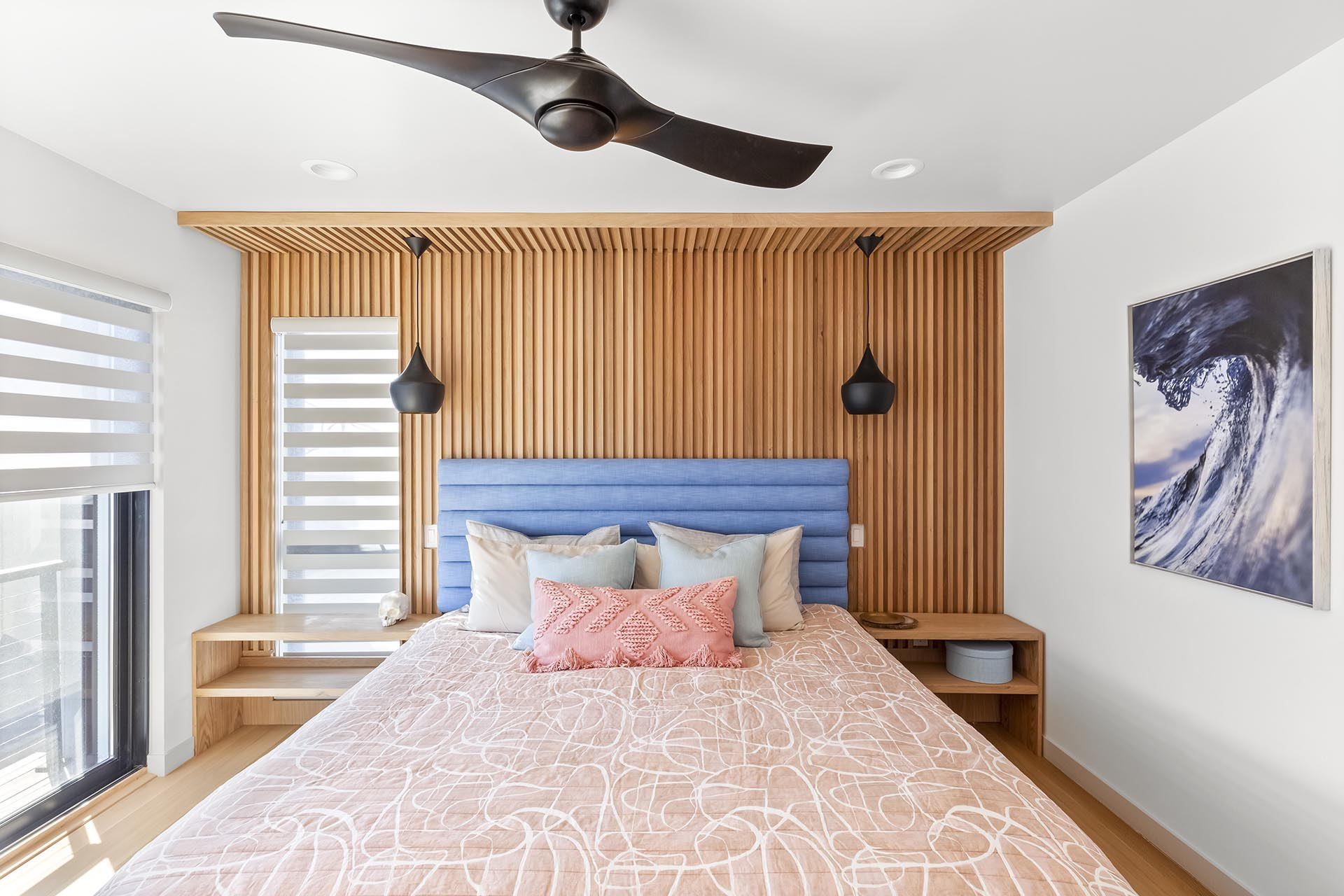 A wood accent wall in this modern bedroom has vertical slats to add a sense of height to the room.