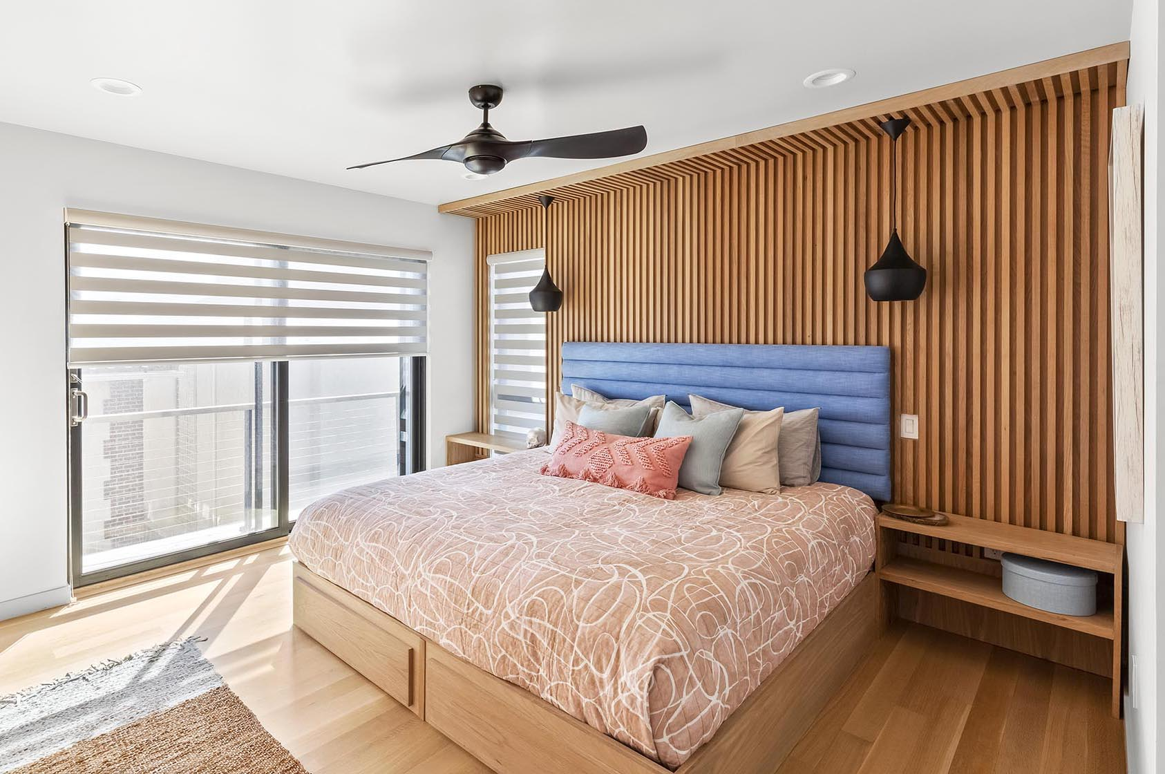 A modern bedroom with a wood accent wall.