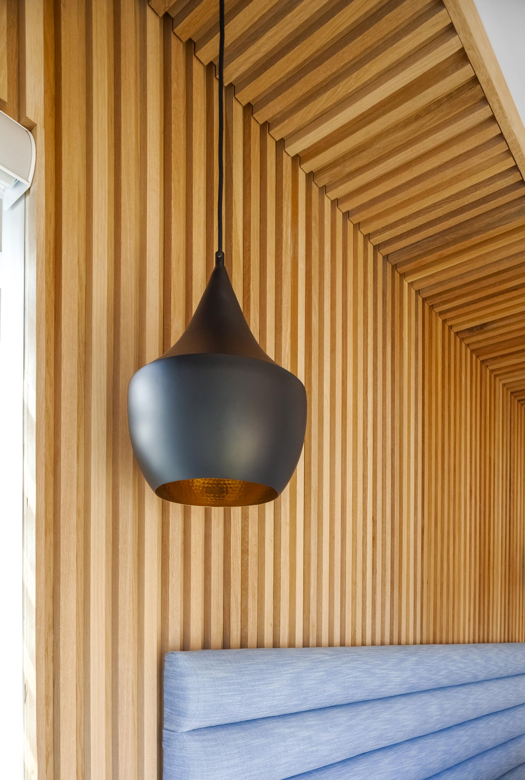 A wood accent wall with a modern black pendant light.