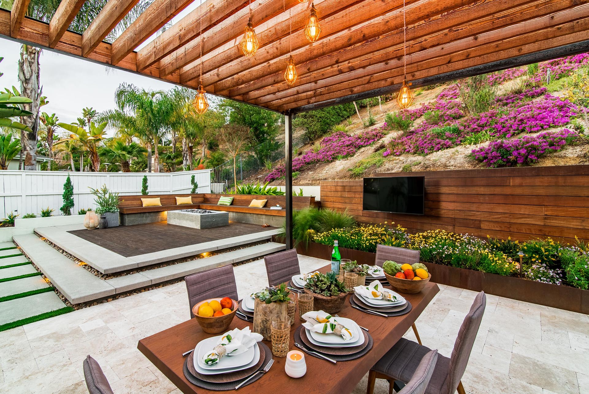 A modern yard with an elevated fire pit, deck, pergola, and outdoor tv.